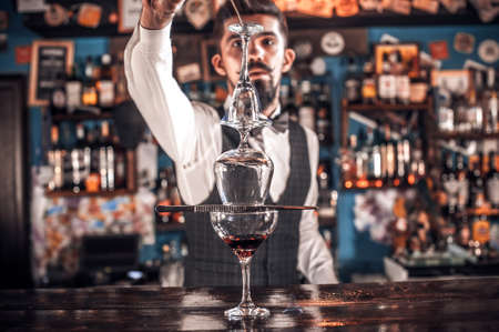 Portrait of bartending demonstrates the process of making a cocktail
