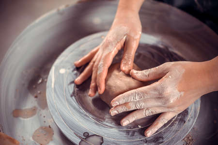 The pottery master shows how to work with clay and pottery wheel. Craft production. Close-up.