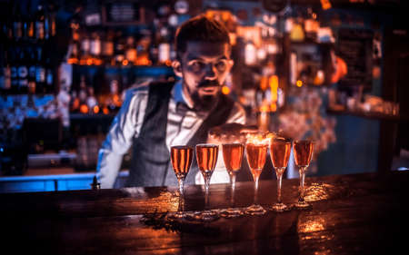 Charismatic bartending pouring fresh alcoholic drink into the glasses behind the bar