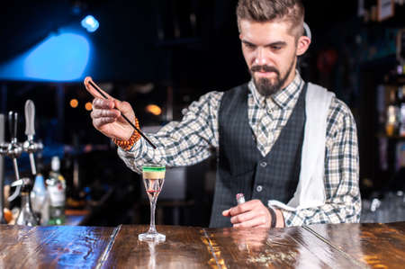 Expert tapster places the finishing touches on a drink while standing near the bar counter in bar