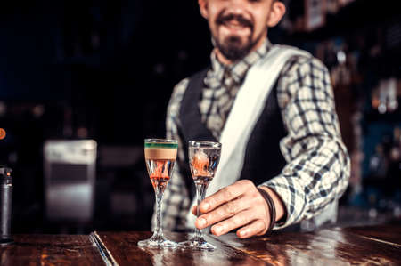 Professional barman decorates colorful concoction while standing near the bar counter in bar Banque d'images