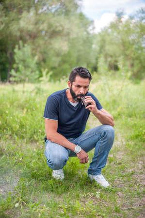 Stylish bearded vaper smokes electronic cigarette exhales smoke. The man smokes.