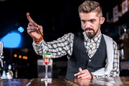Bartender creates a cocktail in the saloon