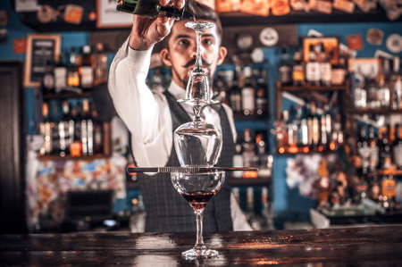 Expert bartender mixes a cocktail in pub