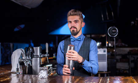 Experienced barman demonstrates the process of making a cocktail while standing near the bar counter in pub