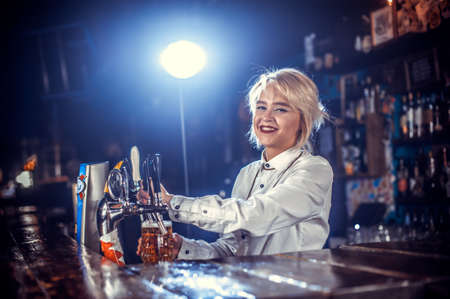 Girl barman mixes a cocktail on the beerhall