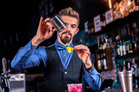 Portrait of bartender intensely finishes his creation in the nightclub