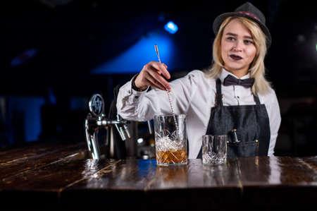 Girl barman makes a cocktail on the bar