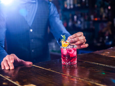 Experienced barkeeper formulates a cocktail while standing near the bar counter in nightclub