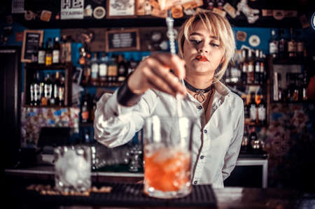 Girl bartender mixes a cocktail in the taproom