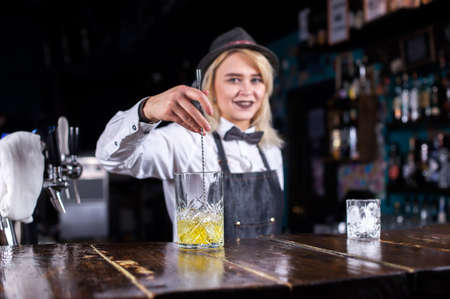 Girl barman makes a cocktail at the taproom