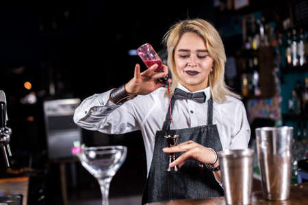 Charming woman bartending mixes a cocktail at the nightclub