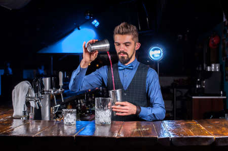 Charming barkeeper intensely finishes his creation in the pub