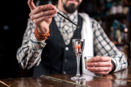 Expert barkeeper is pouring a drink in pub