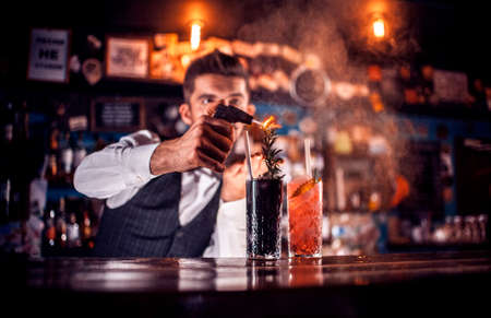 Professional Female bartender intensely finishes his creation at the nightclub