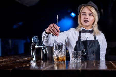 Experienced woman tapster adds ingredients to a cocktail in pub