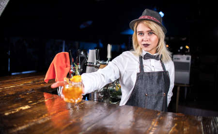 Girl bartender mixes a cocktail behind the bar Banque d'images