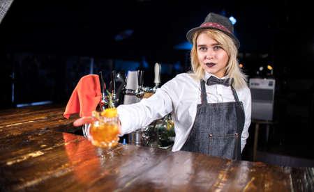 Girl bartender mixes a cocktail behind the bar
