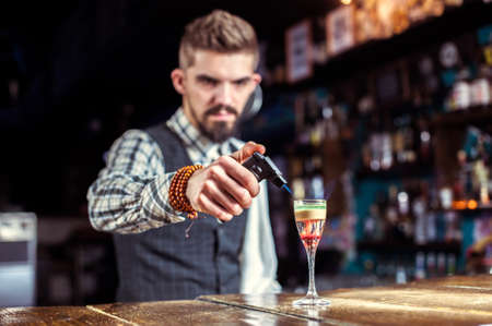 Bartender concocts a cocktail on the porterhouse Stock Photo