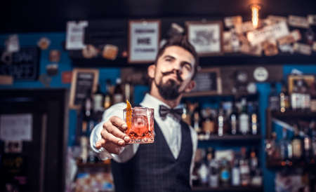 Young barman adds ingredients to a cocktail at the night club