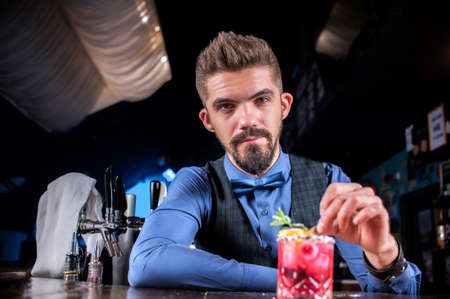 Experienced mixologist adds ingredients to a cocktail behind the bar Banque d'images