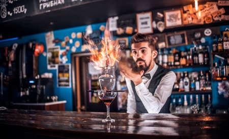 Barman creates a cocktail behind the bar