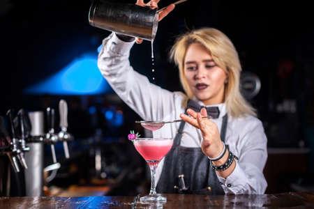 Girl barman mixes a cocktail at the porterhouse