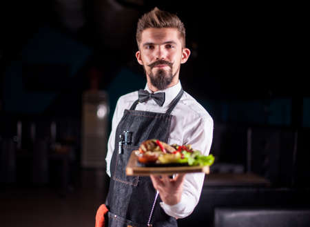 Young restaurant employee serves salad on a black background.