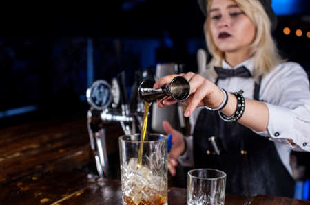 Girl barman makes a cocktail on the pothouse