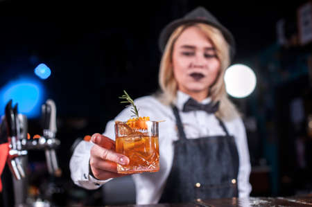 Portrait of girl barman makes a show creating a cocktail