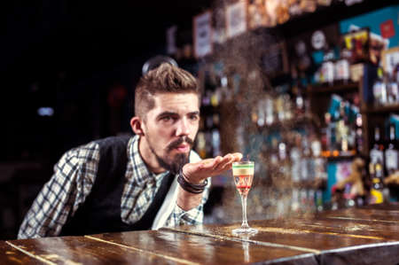 Professional bartending decorates colorful concoction in cocktail bars