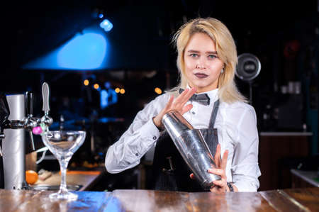 Girl barman creates a cocktail at the beerhall