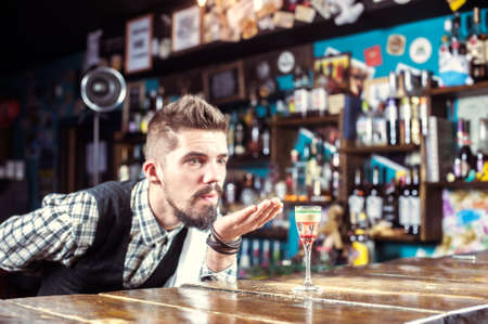 Professional bartender intensely finishes his creation at the night club