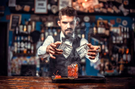 Portrait of bartending demonstrates his skills over the counter at the night club