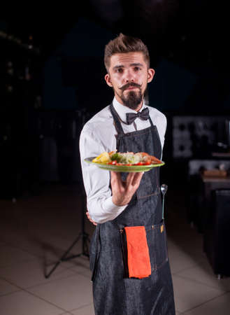 Whiskered restaurant employee carries appetizing dish in the restaurant.