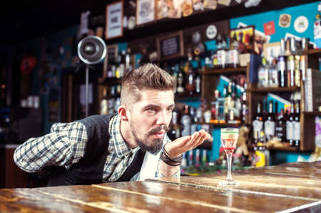 Expert barkeeper makes a show creating a cocktail in the pub