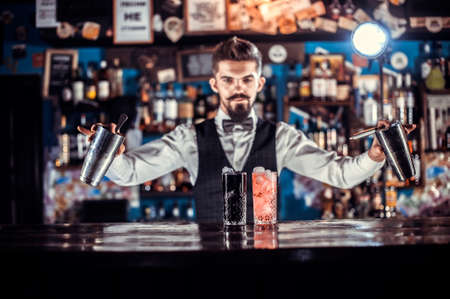 Experienced bartending adds ingredients to a cocktail in the pub