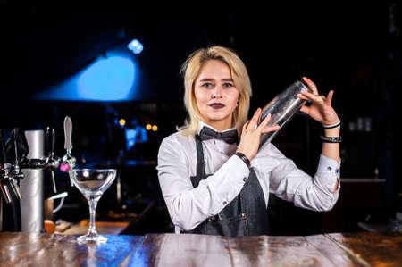 Girl bartender creates a cocktail on the saloon