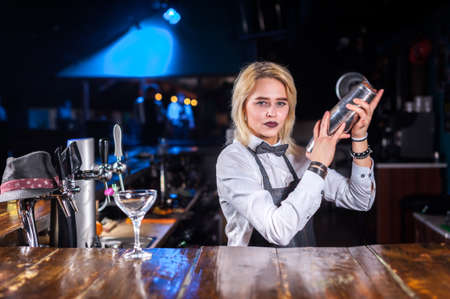 Girl bartender mixes a cocktail on the public house
