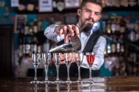 Young bartender demonstrates the process of making a cocktail at the night club Banque d'images