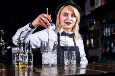 Confident woman bartending adds ingredients to a cocktail at the nightclub