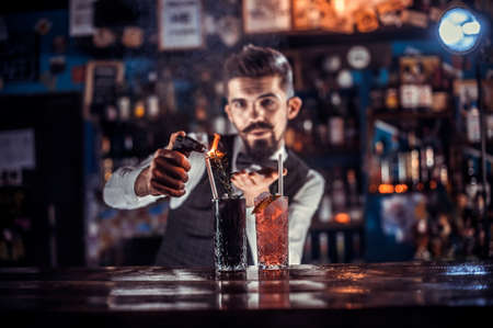 Charming barman is pouring a drink at the bar counter Banque d'images