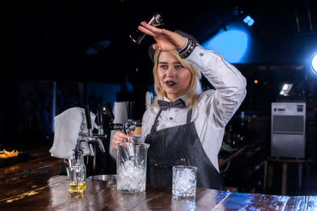 Pretty girl barman intensely finishes his creation while standing near the bar counter in bar Stok Fotoğraf