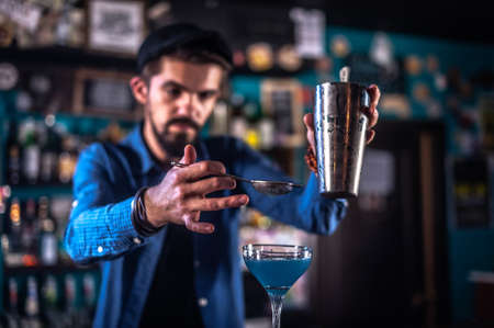Bartender creates a cocktail at the saloon