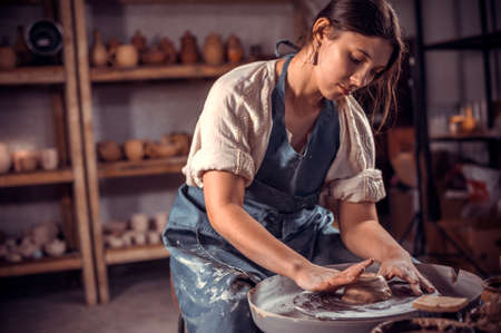 Artisan girl is working on pottery wheel. The concept of craft creativity. Close-up. Stock fotó