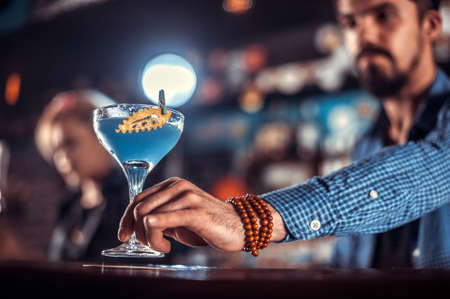 Confident bartender makes a cocktail in the pub