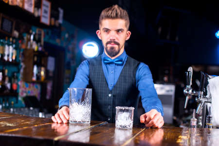 Confident barman makes a cocktail while standing near the bar counter in nightclub