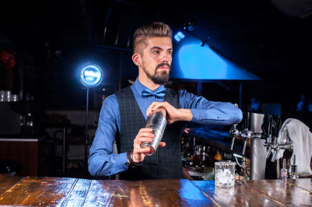 Young bartending places the finishing touches on a drink in the nightclub