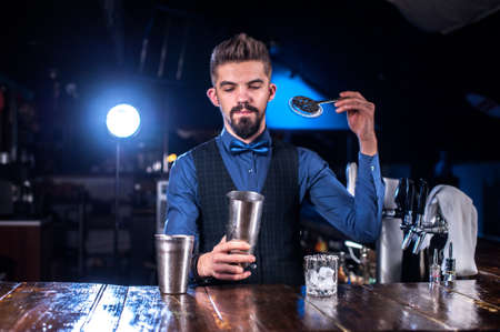 Bartender mixes a cocktail on the public house