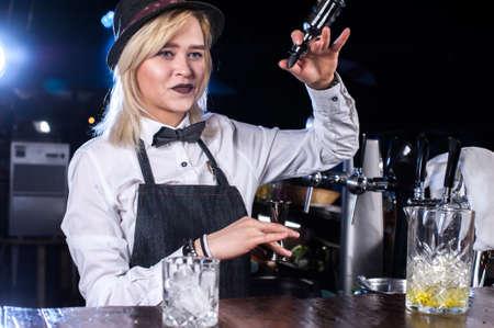 Girl barman makes a cocktail at the beerhouse Reklamní fotografie
